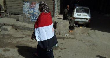 امرأة ترتدى علم مصر وتجوب شوارع فيصل لحث المواطنين على المشاركة بالانتخابات