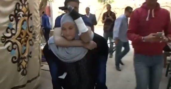مصرية تحمل زوجها المريض ليدلي بصوته في الإنتخابات