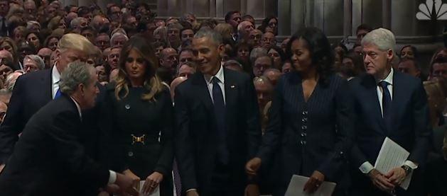 بوش يكرر المشهد ويعطي ميشيل أوباما قطعة حلوي في جنازة والده