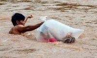 عائلات في فيتنام تسحب أطفالها في «أكياس» بلاستيك بالأنهار الموحلة للذهاب للمدرسة